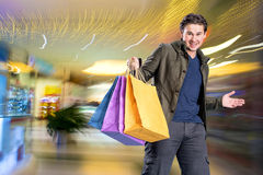 Smiling handsome man with shopping bags Royalty Free Stock Photography