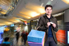 Smiling handsome man with shopping bags and credit card Stock Photography