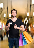 Smiling handsome man with shopping bags and credit card Stock Photos