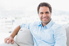 Smiling handsome man sitting on the couch looking at camera Royalty Free Stock Photo