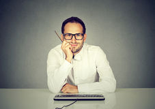 Smiling handsome man sitting in front of computer keyboard Royalty Free Stock Images