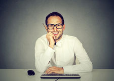 Smiling handsome man sitting in front of computer keyboard Stock Images