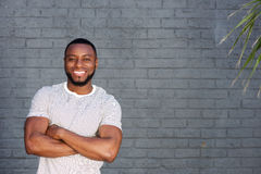 Smiling handsome man standing with arms crossed Stock Photo