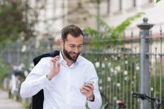 Smiling Handsome Man Using Phone While Walking Stock Photo