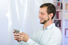 Smiling handsome man using tablet Royalty Free Stock Photography