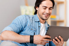 Smiling handsome man using tablet. Modern user. Positive smiling delighted man expressing gladness and using tablet while resting at home stock images