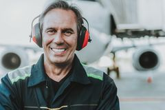 Smiling handsome mechanic standing in front of the huge plane stock photography