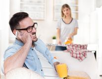 Husband resting on sofa while wife doing chores royalty free stock image