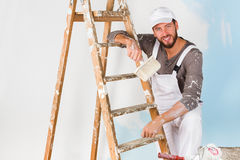 Smiling handsome painter with paint brush Stock Images