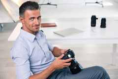 Smiling handsome photographer using camera royalty free stock images
