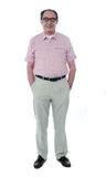 Smiling handsome senior member. With hands in his pocket isolated on white Royalty Free Stock Photo