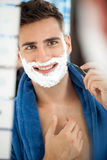 Smiling handsome shaving man. Portrait of smiling handsome shaving man in bathroom stock photos