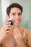 Smiling handsome shirtless man shaving with electric razor Royalty Free Stock Image