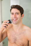 Smiling handsome shirtless man shaving with electric razor Royalty Free Stock Photography