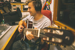 Smiling handsome singer recording and playing guitar Stock Photos