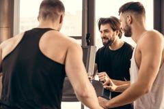smiling handsome sportsmen near treadmill stock images