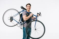 Smiling handsome student holding bicycle on shoulder. On white Royalty Free Stock Photos