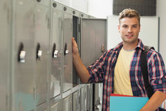 Smiling handsome student standing next to locker Royalty Free Stock Photos