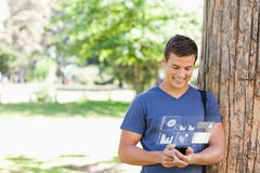 Smiling handsome student using his digital smartphone Royalty Free Stock Photos