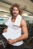 Smiling handsome trainer with clipboard in gym. Portrait of a smiling handsome trainer with clipboard standing in the gym Stock Images