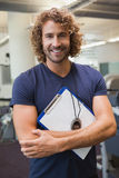 Smiling handsome trainer with clipboard in gym. Portrait of a smiling handsome trainer with clipboard standing in the gym Royalty Free Stock Photos
