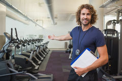 Smiling handsome trainer with clipboard in gym. Portrait of a smiling handsome trainer with clipboard standing in the gym Royalty Free Stock Image