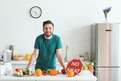 Smiling handsome vegan man standing near kitchen counter with vegetables and no. Meat sign royalty free stock photos