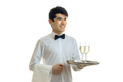 Smiling handsome waiter with black hair and shirt holding a tray with two glasses of wine Royalty Free Stock Photography