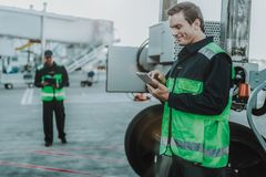 Smiling handsome worker looking something in tablet royalty free stock images