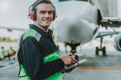 Smiling handsome worker standing in front of huge plane stock image