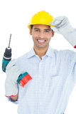Smiling handsome young handyman in hard had with drill Royalty Free Stock Image