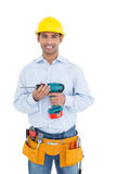 Smiling handsome young handyman in hard hat holding drill Royalty Free Stock Photo