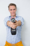 Smiling handsome young handyman holding drill Stock Photography