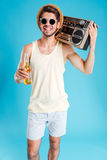 Smiling handsome young man with boombox and bottle of beer. Smiling handsome young man in hat and sunglasses with boombox and bottle of beer Royalty Free Stock Photo
