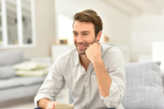 Smiling handsome young man drinking coffee at home Royalty Free Stock Images