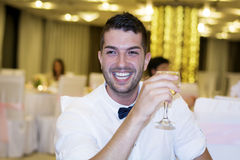 Smiling handsome young man with  glass of wine in hand. Handsome man toasting with white wine in a restaurant - best man Stock Photo