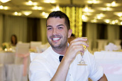 Smiling handsome young man with  glass of wine in hand Royalty Free Stock Photo