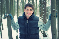 Smiling handsome young man holding trees Royalty Free Stock Photo