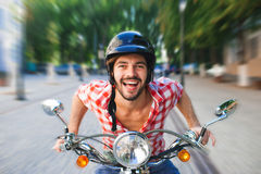 Smiling handsome young man riding scooter royalty free stock photo