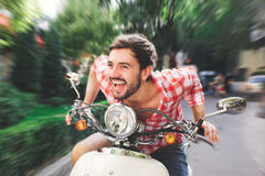 Smiling handsome young man riding scooter Stock Images