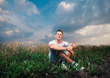 Smiling handsome young man sitting on on the green grass on a ba Royalty Free Stock Photos