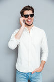 Smiling handsome young man in sunglasses talking on mobile phone Royalty Free Stock Image
