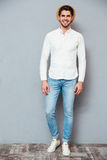 Smiling handsome young man in white shirt, jeans and hat Royalty Free Stock Photos