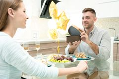 Happy man making gift for beloved woman stock photos