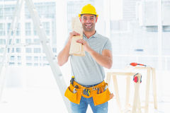 Smiling handyman carrying planks in building royalty free stock photography