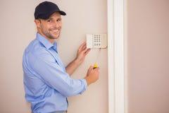 Smiling handyman fixing an alarm system stock photography