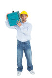 Smiling handyman in hard hat carrying a toolbox Stock Image