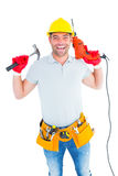 Smiling handyman holding hammer and drill machine Stock Image
