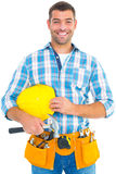 Smiling handyman holding hardhat and hammer Royalty Free Stock Photos