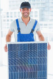 Smiling handyman holding solar panel in bright office Stock Photography